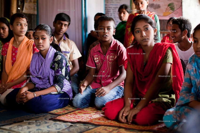 "Oli Ahmed (11, in pink shirt) speaks during a monthly meeting of a Children's Group in Bhashantek Basti (Slum) in Zon H, Dhaka, Bangladesh on 23rd September 2011. Oli says, ""We are in extreme poverty. If our parents get a good price for our marriages, there is nothing we can do. (Also,) we are now in the era of gender equality and girls should be allowed to study instead of being married off."" Oli wants to be a doctor when he grows up. The Bhashantek Basti Childrens Group is run by children for children with the facilitation of PLAN Bangladesh and other partner NGOs. Slum children from ages 8 to 17 run the group within their own communities to protect vulnerable children from child related issues such as child marriage. Photo by Suzanne Lee for The Guardian"