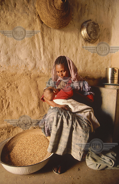© Betty Press / Panos Pictures..Near Asmara, ERITREA..Woman breastfeeding her baby at home.