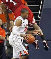 Virginia forward Akil Mitchell (25) is fouled by North Carolina State forward Richard Howell (1) during the game Saturday in Charlottesville, VA. Virginia defeated NC State 58-55.