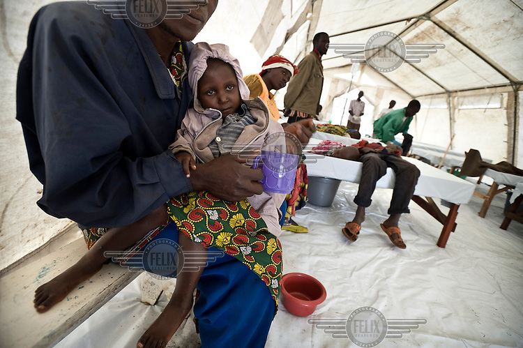 People inside the Medecins Sans Frontieres (MSF) tent in the Kibati camp for displaced people wait to recieve re-hydration fluids. MSF started a cholera treatment centre after cholera was diagnosed in the local health centre. Due to the new influx of displaced people after violence, Kibati camp is now overcrowded and the water and sanitation situation is deteriorating. An outbreak of cholera could be a further threat to many lives.
