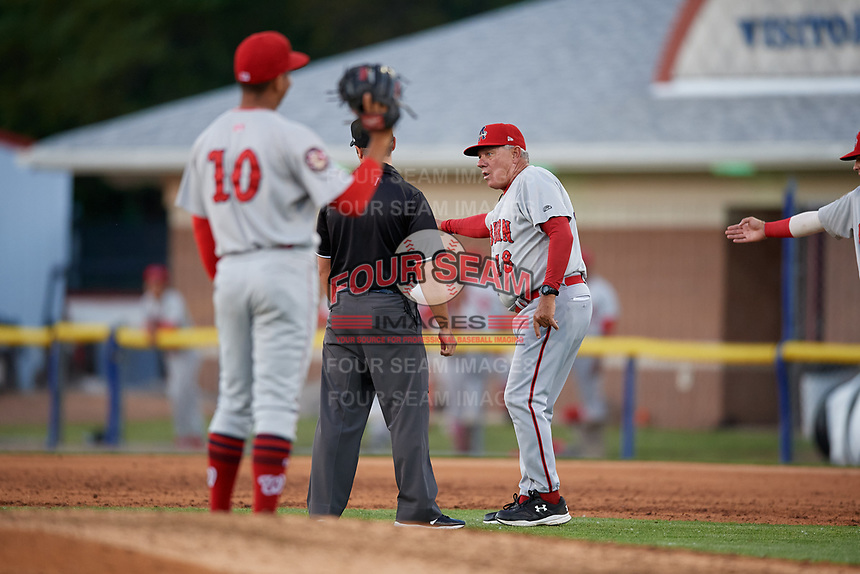 Auburn Doubledays manager Rocket Wheeler (18) argues a call with umpire Paul Roemer as pitcher Gilberto Chu (10) looks on during a NY-Penn League game against the Batavia Muckdogs on June 18, 2019 at Dwyer Stadium in Batavia, New York.  Batavia defeated Auburn 7-5.  (Mike Janes/Four Seam Images)