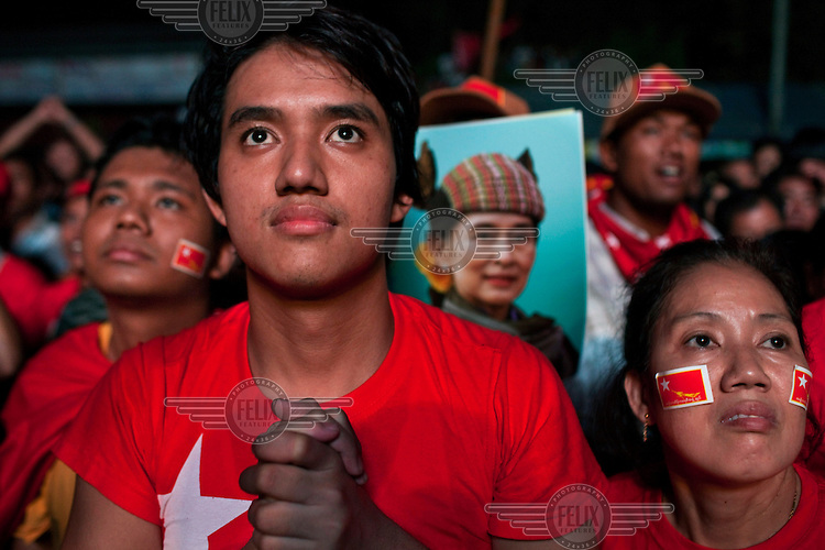 National League for Democracy (NLD) supporters look hopefull outside the NLD headquarters as they watch results come in for the by-elections in Yangon. A poster of Aung San Suu Kyi is being held up.