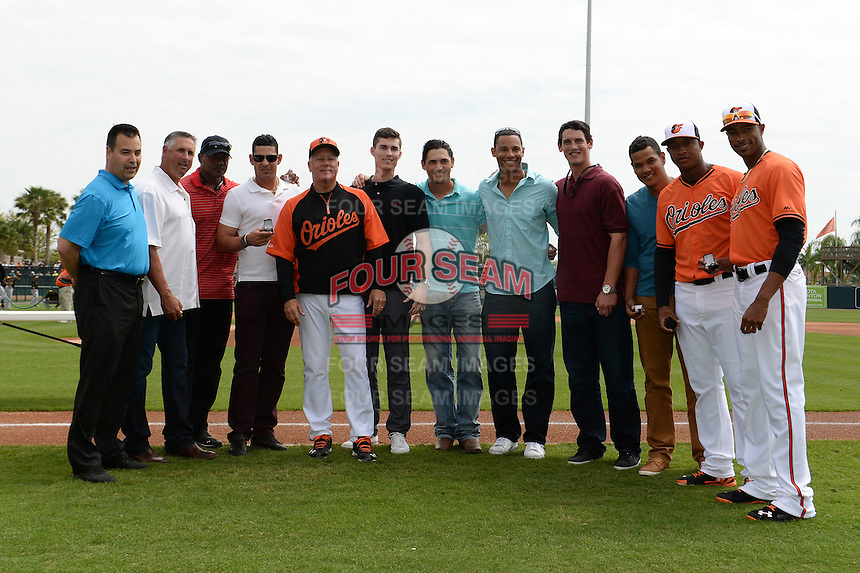 Baltimore Orioles Dan Duquette, Gary Kendall, Alan Mills, Dariel Alvarez, Brian Graham, Tim Berry, Jason Gurka, Branden Kline, Michael Ohlman, Eduardo Rodriguez, Jonathan Schoop, Henry Urrutia pose for a photo after being presented with their Arizona Fall League Championship rings before a spring training game against the Pittsburgh Pirates on March 23, 2014 at Ed Smith Stadium in Sarasota, Florida.  Baltimore and Pittsburgh tied 7-7.  (Mike Janes/Four Seam Images)