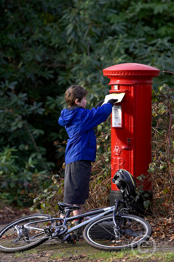 Josh posting letter into red postbox  in  School uniform with school backpack and Islabike bicycle lying next to him on ground..Virginia Water , Surrey   February 2008..