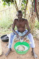 N. Uganda, Kitgum District. Peter C. Alderman Foundation project. Man washing his laundry whiel his wife sorts sorghum.