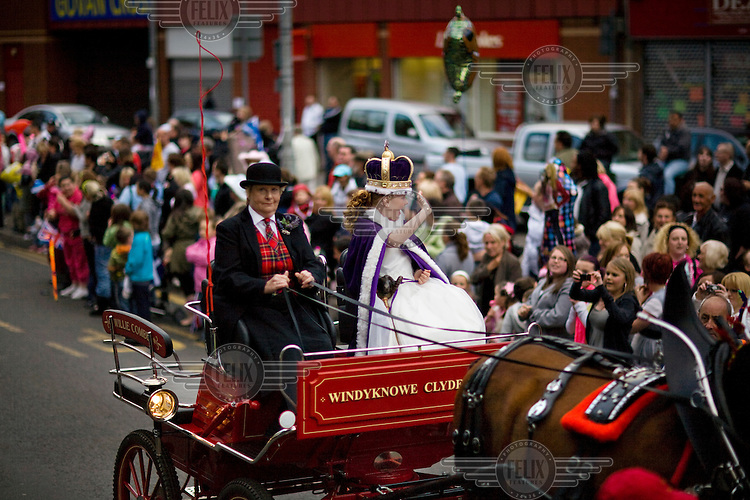 The Govan Fair Queen travels by horse and cart down a street. This year's queen, 11 year old Abbie Hunter from Govan, Glasgow, will begin a year of duties in the local community.