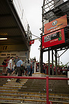 Home supporters making their way past the electronic scoreboard on the Ealing Road terrace after Brentford hosted Leeds United in an EFL Championship match at Griffin Park. Formed in 1889, Brentford have played their home games at Griffin Park since 1904, but are moving to a new purpose-built stadium nearby. The home team won this match by 2-0 watched by a crowd of 11,580.