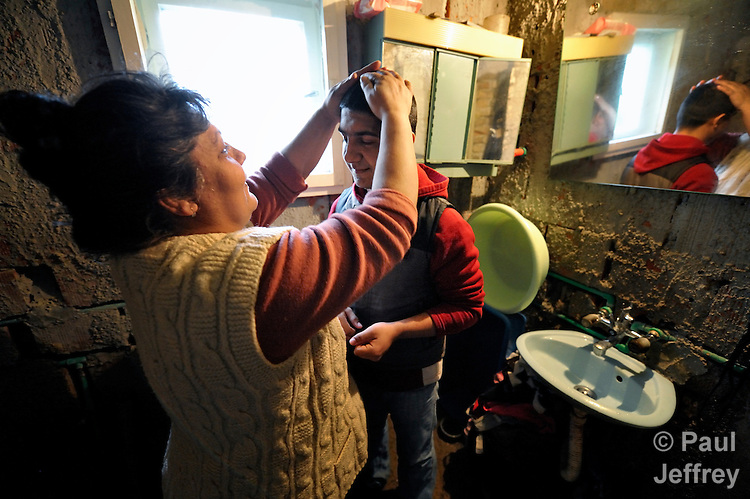 Bajram Kruezi's mother, Sabahata, smoothes his hair as he prepares to leave home in the morning in the Zemun Polje neighborhood of Belgrade, Serbia, on his way to the Branko Pesic School, an educational center for Roma children and families which is supported by Church World Service. Kruezi's family came to Belgrade as refugees from Kosovo, and like many Roma can't afford regular school fees. Many Roma also lack legal status in Serbia, and thus have difficulty obtaining formal employment and accessing government services. Kruezi wants to be a Muslim religious scholar when he grows up.