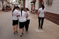 Daytime landscape view of four women wearing uniforms walking down a small road in Bozhou in Qiáochéng Qū in Anhui Province.  © LAN