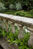 An elegant stone balustrade overlooking the sunken garden is planted with jasmine and white roses