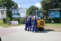 Men wearing blue suspender like trouser uniforms working with a tracked construction vehicle.  Warsaw Poland