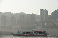 Daytime landscape view of an automobile ferry on the Cháng Jiāng with commercial buildings in the background in the Wànzhōu District in the Chongqing Municipality.  © LAN
