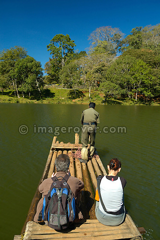 India, Kerala, Periyar/Kumily, Periyar Tiger Reserve.  Two western tourists in the Periyar Tiger Reserve crossing the Periyar Lake by raft with their local indian guide. No releases available.