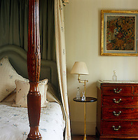 In this bedroom a mahogany chest-of-drawers glows against the warm tones of the wall behind which has been painted in an antique finish