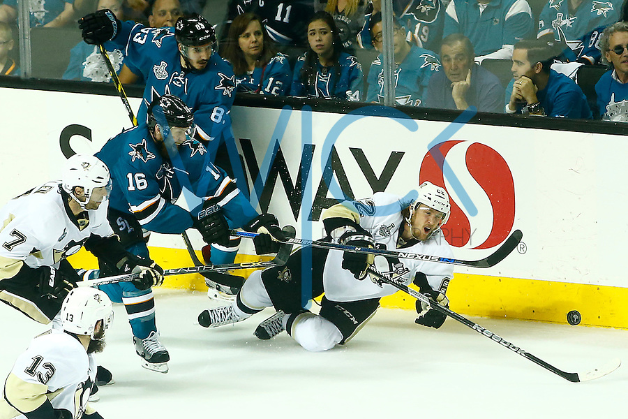 Carl Hagelin #62 of the Pittsburgh Penguins reaches for a loose puck in front of Nick Spaling #16 of the San Jose Sharks during game three of the Stanley Cup Final at the SAP Center in San Jose, California on June 4, 2016. (Photo by Jared Wickerham / DKPS)