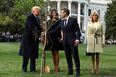 U.S. President Donald Trump and France's president Emmanuel Macron shake hands after planting a tree, a gift from the President and Mrs. Macron, with First Ladies Melania Trump and Brigitte Macron on the South Lawn of the White House in Washington, D.C., U.S., on Monday, April 23, 2018. As Macron arrives for the first state visit of Trump's presidency, the U.S. leader is threatening to upend the global trading system with tariffs on China, maybe Europe too. <br /> Credit: Yuri Gripas / Pool via CNP