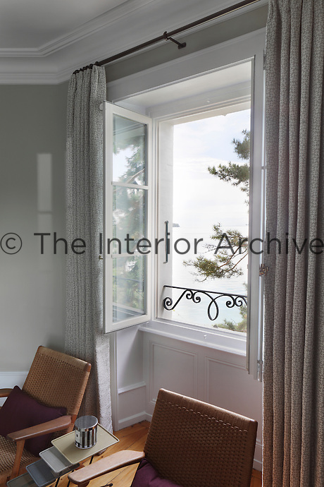 A pair of woven armchairs sit under the open window of this bedroom which has views over the lake