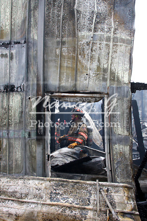 A firefighter framed in a window of a fire collapsed building