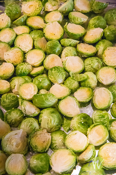 Brussel sprouts on tray prepared for roasting. Oiled and peppered.