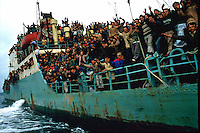 Brindisi, 8 Marzo, 1991. Una delle prime navi cariche di Albanesi in navigazione verso il porto di brindisi. Migliaia di Albanesi arrivarono al porto di Brindisi utilizzando ogni tipo di imbarcazione, dopo la caduta del regime comunista in Albania. A boat people arrive at the Brindisi harbor. It was March 8, 1991 when thousands of albanian refugees reached Italy after the fall of the comunist regime. The city of Brindisi, south Italy was invaded by a mass of desperate and poor people.