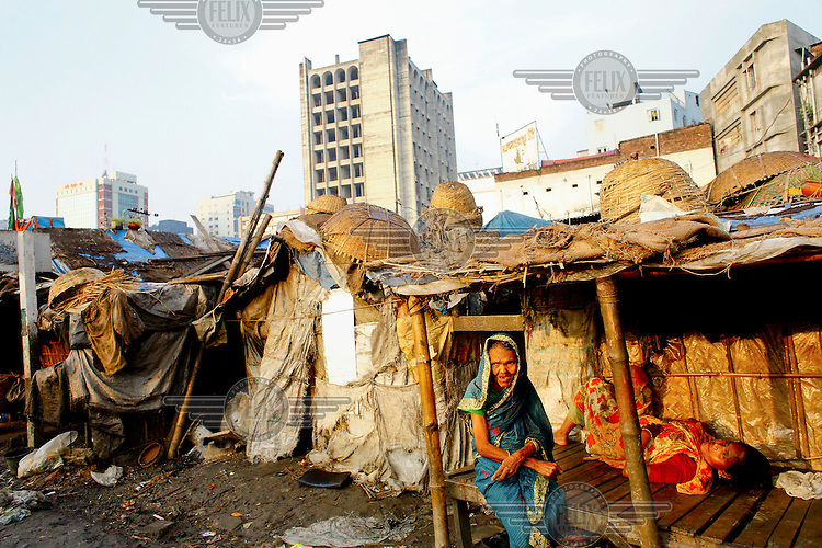 An elderly woman sits outside her makeshift shack in one of the city's slum districts. It is thought that more than six million people live in slums in Dhaka.