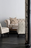 White armchairs and sofa in industrial space with wooden flooring