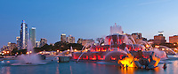 Buckingham Fountain's light show glows at dusk with the One Museum Park buidling stands tall in the background
