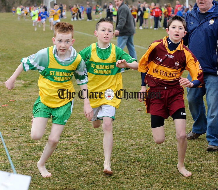 Jack Lynch and James Harty of Shannon tussle for position at the finish line with James Harrison of Tulla  at the Èast Clare Primary Schools Cross Country Championships at Lees Road. Photograph by John Kelly.