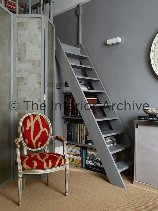 A lacquered screen painted in silver leaf conceals the kitchen which is located beneath the small gallery library