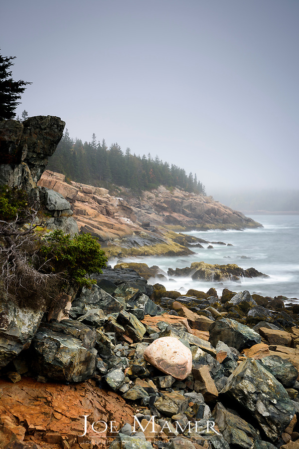 Foggy morning and rocky shoreline of Western Point in Acadia National Park.