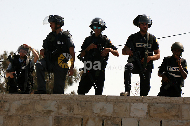 Israeli police stand guard as Palestinian Muslims pray on the streets of the Wadi al-Joz neighbourhood in east Jerusalem during the Friday prayers following restrictions by Israeli police preventing Palestinians under 40 years old from entering the Al-Aqsa mosque compounds, on October 16, 2015. Israeli security forces deployed massively in Jerusalem as Jews armed themselves with everything from guns to broomsticks, rattled by a wave of Palestinian attacks that have shaken the country. Photo by Mahfouz Abu Turk