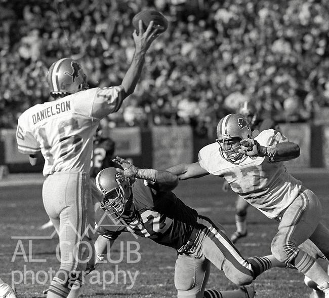 San Francisco 49ers vs. Detroit Lions at Candlestick Park Saturday, December 31, 1983..49ers beat the Lions 24-23.Detroit Lions Quarterback Gary Danielson (16) passes as .San Francisco 49ers Defensive End Jeff Stover (72) rushes him.  Detroit Lions Guard Don Greco (67).