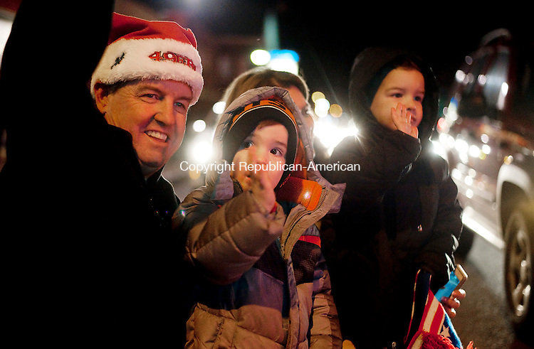 WINSTED, CT--- -121915JS08--Kurt vonTillow along with his grandsons,  Jordan Giampaolo, 2, Carter  Giampaolo, 4, and  Sandy Giampaolo, watch and wave as the 11th annual Winsted Fire Department &quot;Gator&quot; Christmas Parade passes by on Saturday. The parade continues to honor the tradition of former firefighter Gaeton &quot;Gator&quot; Gangi who started the parade in 2004 as a community Christmas parade. <br /> Jim Shannon Republican-American