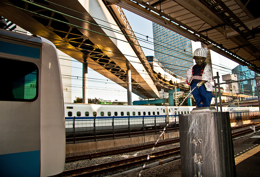 Hamamatsucho station`s wee boy statue is dressed for a festival as passing Monorail, Bullet & metro trains speed by. The Wee Boy is dressed by local ladies depending on seasons & events.