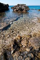 """Scogliera di Porto Selvaggio - Reportage fotografico di Alessandro Caniglia, Alessandro De Matteis e Dario Luceri - Il Parco Naturale Regionale di Porto Selvaggio è situato lungo la costa ionica e ricade nel comune di Nardò (Lecce). Definito come """"area di notevole interesse pubblico"""" già nel 1939, è stato effettivamente istituito come Parco nel 2004. I suoi limiti sono compresi tra la baia di Frascone (a nord) e la Torre dell'Alto (a sud). Ha una estensione complessiva di circa 1000 ettari.Porto Selvaggio è una delle zone tra le più incontaminate del litorale Ionico, con un paesaggio caratterizzato da una pineta di ca. 300 ettari e da una macchia mediterranea ricca di acacee e ginestre..Lungo la costa sono presenti molte cavità carsiche, con varie insenature, grotte sommerse.Per gli amanti della natura il paesaggio è estremamente suggestivo in ogni stagione: molto silenzioso e rilassante in autunno, inverno e primavera, ricco di colori e festoso in estate, con il canto delle cicale che accompagna i visitatori lungo i sentieri e di tratti di scogliera che portano fino alla spiaggia. Il mare limpido e azzurro, con un fondale ricco di flora e fauna marina, è spesso meta di numerosi subacquei."""