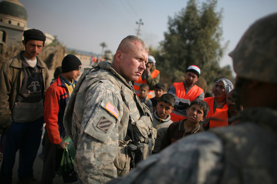"Lt. Col. Kenneth Adgie, commander of 1-30 Infantry 3rd Infantry Division, visits his officers and men and speaks with locals after a company from his battalion has carried out an ""air assault"" by helicopters to move into a village south of Baghdad in the Arab Jabour area. They operation inaugurated the creation of a ""concerned local citizen"" presence in a village previously held and used by Sunni insurgents."