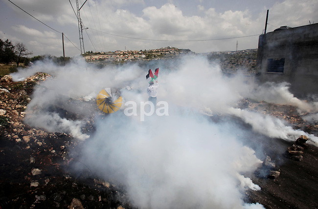 A Palestinian protester waves his national flag amid tear gas cloud during clashes with Israeli security forces following a protest Palestinian Prisoner's Day and against the expropriation of Palestinian land by Israel in the West Bank village of Kafr Qaddum, near the northern city of Nablus, April 17, 2015. The current number of Palestinians held in Israeli prisons is at least 6,200 and is the biggest for at least five years, according to figures from rights groups. Photo by Nedal Eshtayah