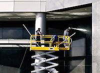 Mannen op een hoogwerker spuiten de gevel schoon.