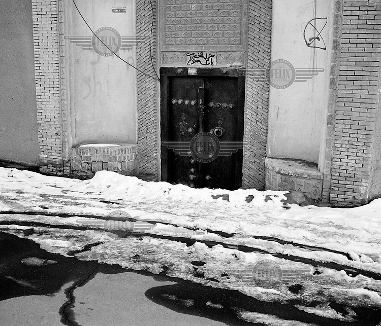 A heavily built door and a snow covered street in Kashan.