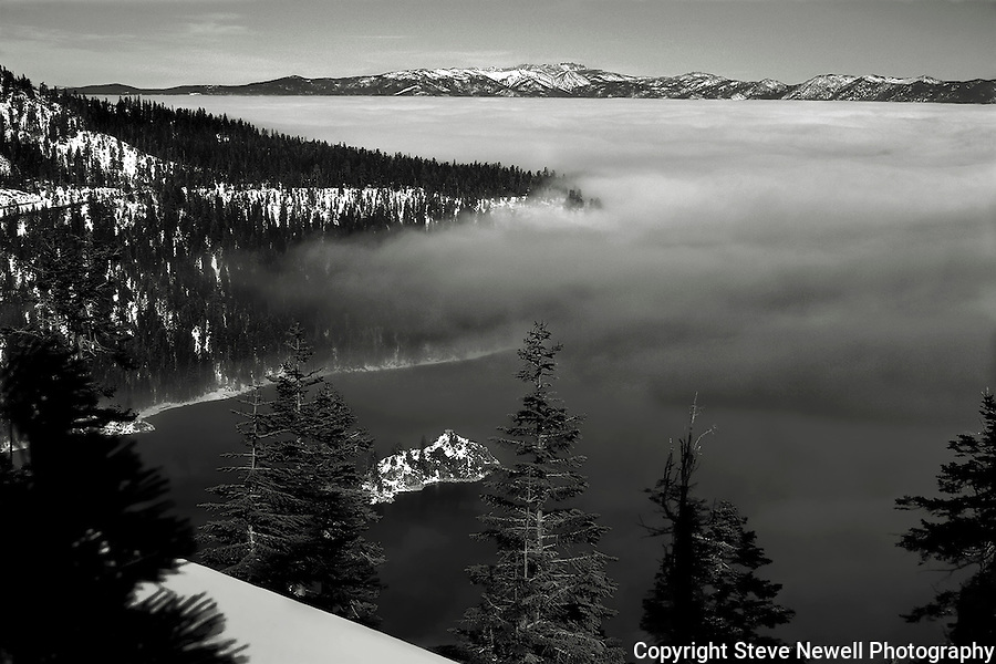 """Into the Mist"" Emerald Bay- Lake Tahoe CA. MY first two photo sessions of Emerald Bay came in 2005 when a layer of clouds hovered over the lake for three weeks. I finally went out to Emerald Bay and hiked up till I got above the clouds. On the first day, Fannette Island was completely covered under the fog as pictured in ""Undercover"".  The next day I came back and hiked up to the same spot. I couldn't believe my eyes. The fog had dissipated just a little bit leaving Fannette Island in view with Lake Tahoe covered under the fog and blue bird skies above. The snow capped mountains surround the entire basin. Into the Mist is a ""One of a Kind"" photograph of Lake Tahoe's ""Jewel of the Sierra""- Emerald Bay"