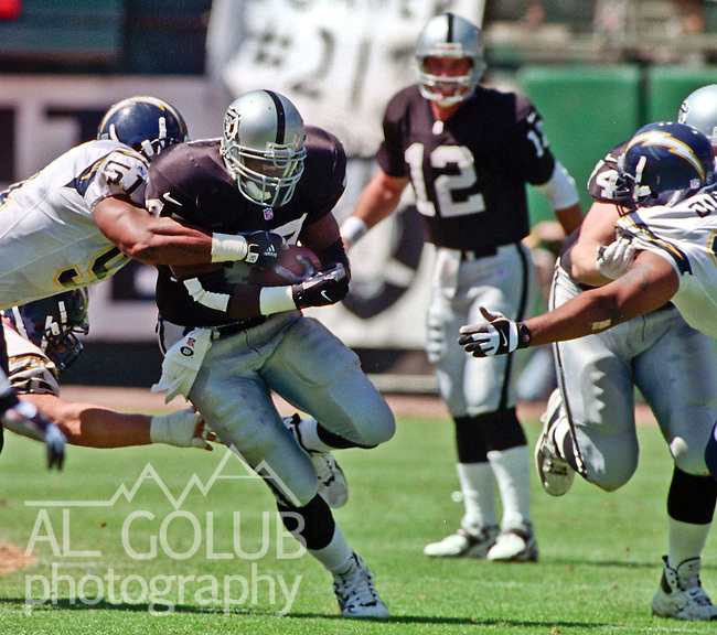 Oakland Raiders vs. San Diego Chargers at Oakland Alameda County Coliseum Sunday, September 3, 2000.  Raiders beat Chargers  9-6.  San Diego Chargers linebacker Gerald Dixon (51) tackles Oakland Raiders running back Tyrone Wheatley (47).