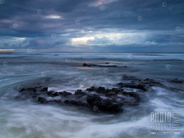 Waves roll over and around protruding rocks along the shore at Pine Trees Beach, Big Island.