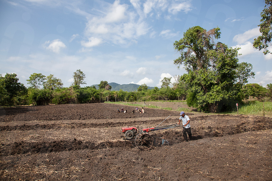 A family works to prepare their corn field for planting before they were made to relocated from their land. The family complained that the compensation provided by the Government for the relocation was not adequate. Omliang, Kampong Speu, Cambodia. 13 May. 2010. © Nicolas Axelrod / Ruom