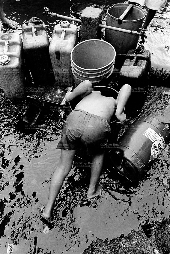 Philippines. Luzon Region. Manila. Tondo area. Smokey mountain is a rubbish dump. Life on a garbage heap. A young boy puts his head inside a plastic bucket. Various water tanks are waiting on line to collect water during the hours of available water distribution. Tabs. © 1992 Didier Ruef .