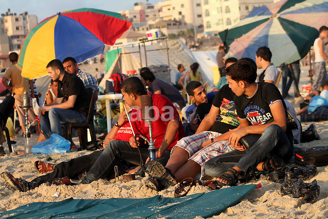 Palestinian youths smoke the water pipes on the beach on their week-end in the Mediterranean sea in Gaza City on July 06, 2012. Photo by Ashraf Amra