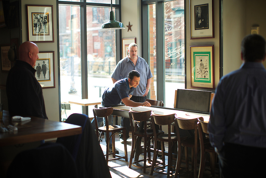 Jersey City, NJ - January 14, 2016: Customers play shuffleboard by the bar at Greene Hook. CREDIT: Clay Williams for Edible Jersey.<br /> <br /> <br /> &copy; Clay Williams / claywilliamsphoto.com