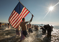 BROOKlLYN, NY - JANUARY 01 : A man with a flag enters in the water during the annual Coney Island Polar Bear Club New Year's Day swim by running into the ocean at Coney Island , Brooklyn on January 01, 2017. Photo by VIEWpress/Maite H. Mateo.