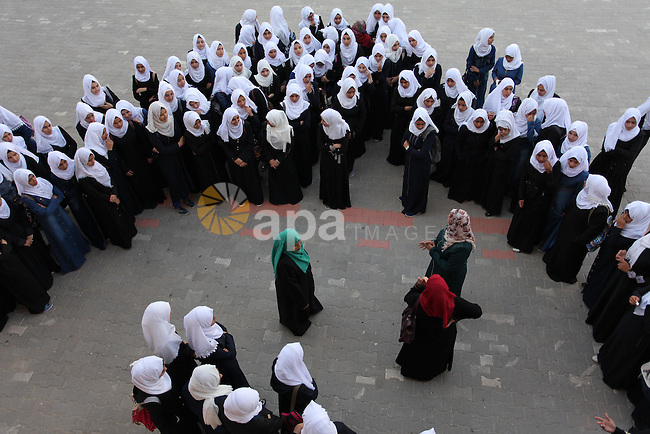 Palestinian schoolgirls play exercises inside their school in the morning of the first day of the new year study in Khan Younis in the southern Gaza Strip August 28, 2016. The mural reads. Photo by Ashraf Amra