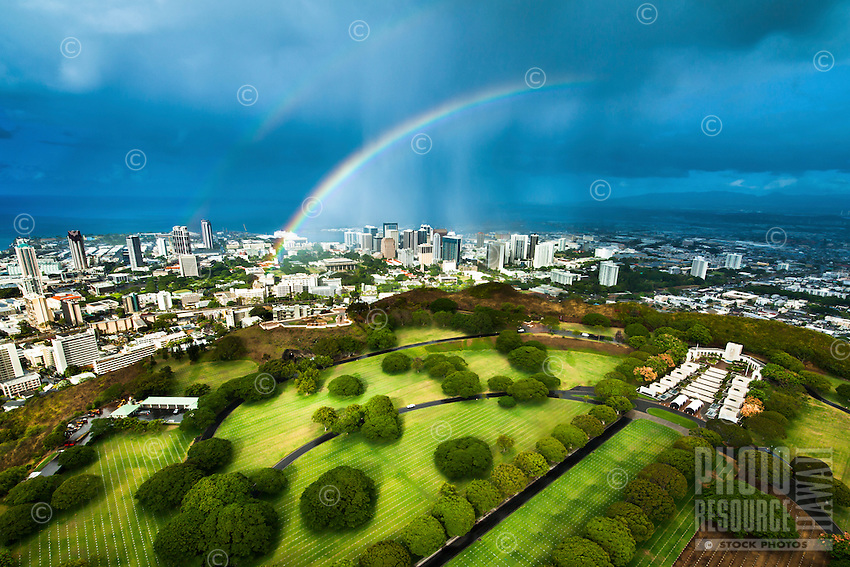 An aerial perspective of Punchbowl Cemetery with a big double rainbow touching down over downtown Honolulu on O'ahu, with dark blue storm clouds on the right.