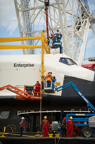 Workers attach a sling to the space shuttle Enterprise in order to lift it off of a barge and onto the Intrepid Sea, Air and Space Museum where it will be permanently displayed, Wednesday, June 6, 2012 in New York. .Mandatory Credit: Bill Ingalls / NASA via CNP